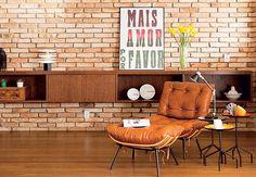 """Os tijolos de demolição cortados pela metade foram aplicados sobre a parede branca original da sala de 49 m² neste apartamento em Pinheiros, São Paulo. """"Ficou igual à dos lofts de Nova York, como pediu o jovem morador"""", diz a arquiteta Nicole Finkel. """"Ele não quis qualquer acabamento porque gosta da rusticidade do tijolo"""""""