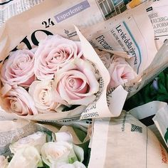 How lovely - pale roses wrapped in a news print. Photo - Crush Cul de Sac