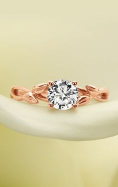 Wispy vines and delicate buds of precious metal entwine toward a brilliant center gem in this nature-inspired ring.