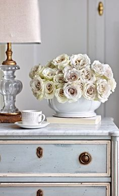 It's all here. White on white vignette. Gold and crystal lamp. White roses. White china. White marble. Gustavian gray chest.