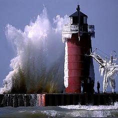 Faro con una ola que alcanza casi su altura.
