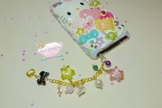 This keychain has a clear dust plug with a gold link chain filled with acrylic stars, faux crystals, plastic black bow and a kitty charm.    There is also a color bell attached.    Picture shows my ipod which was decoden by Kawaii X Couture. She sells custom decoden phone cases and other kawaii p...