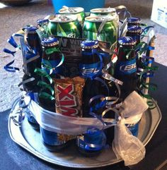 Awesome gift for a boyfriend/husband/dad. Made this Bud Light & Mountain Dew cake for Richie's birthday. 10 bottles of Bud Light, 8 cans of Mountain Dew, 4 chocolate bars and 4 Bombers scratch tickets on top of an old pizza tray spray painted silver! Got the idea from other pins and adapted it. Bought 12 packs of the drinks and put ribbons on the extra drinks to give to him. Love love love!
