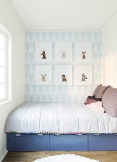 Adorable kids' bedroom with geometric printed walls, pom pom embroidered duvet cover, under the bed storage, hardwood floors, and framed prints   Photos by Sharon Montrose of The Animal Print Shop