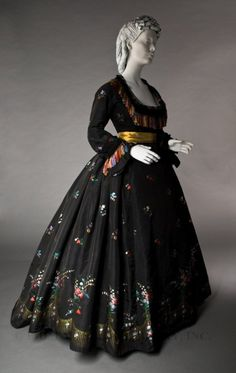 An evening dress from the 1860s made of silk taffeta. Taffeta was an extremely popular material throughout the 19th century and was used in men and women's clothing especially skirts and petticoats. It was known as 'rustling silk' because of the sound it made when moved and was often bought because of this quality.