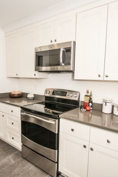 Stainless steel appliances with under cabinet lighting over range, new cabinetry & Milan Grey Quartz Countertop