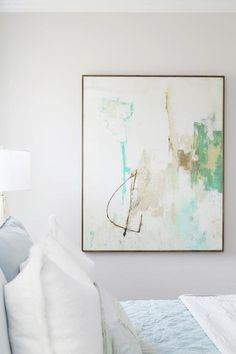 An aqua and green abstract painting brings life to a white wall in this gorgeous white and blue bedroom featuring a bed dressed in white and blue bedding topped with matching pillows. Blue Bedding, Blue Bedroom, Watercolor Paintings Abstract, Abstract Art, How To Dress A Bed, Art Projects For Teens, Coastal Bedrooms, Contemporary Bedroom, Beach Art