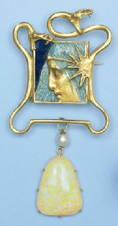 An Art Nouveau pendant, by René Lalique, circa 1900. Depicting a female face in profile within a frame of serpents, suspending an opalescent glass pendant surmounted by a pearl, mounted in gold. #Lalique #ArtNouveau #pendant