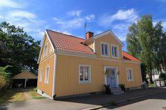 Yellow house in Sweden, clay coloured roof, grey door