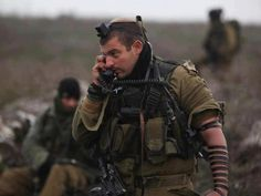 """Only in Israel! This awesome photo shows the true strength of the Israeli Army! This soldier's right hand connects him to his commander, his left to his Creator. """"For it is the Lord your God, Who goes with you to battle your enemies for you to save you."""""""