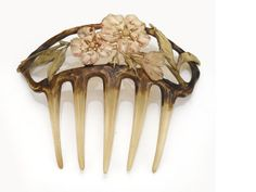 An art nouveau carved horn hair comb, circa 1915 painted floral motif; dimensions: 4 1/2 x 4in.