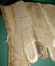 "Stays, Ebay Auction c.2004  This is a rare 1740-1760 early American colonial time period corset/stays. Made of two tone tan linen that is laid over what is probably rows of cane that are tightly hand stitched into place. A band of thin cotton extends down the front seam. The top edge and bottom hem and flaps are lined with kid leather. The inside is lined with heavy tan homespun linen. Bust 34"". Waist 26"". Front length 12"". Back length 13.5""."