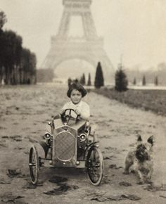 Amazing photograph of a little girl in a fabulous toy car, her dog running beside her and oh ya, the Eiffel Tower!