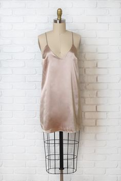 Channel a softer mood this season with this lovely blush-hued slip dress, designed with a sleek, silk-like fabric. It falls to the mid-thigh in a mini cut, and is made with a loose-fitting silhouette.