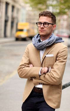 beige blazer, black pants, white shirt and a scarf.