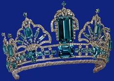 When first made in 1957, the tiara consisted of the three upright rectangular stones (detachable for use as brooches), mounted on a simple platinum band. The large central stone was originally the pendant of the necklace given to The Queen by the President and People of Brazil in 1953 as a Coronation present. In 1971 the tiara was adapted to take four scroll ornaments from an aquamarine and diamond jewel given to The Queen by the Governor of São Paulo in 1968.