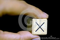 Left hand picking-up a wooden boxes with sign x on black background.