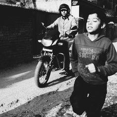 Streets of Kathmandu 11 Young boy running on the street. Motorcycle. Street photography. Nepal. Kathmandu. Black & White.