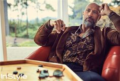 Dwayne Johnson in a Polo Ralph Lauren bomber, an Etro shirt, and Giorgio Armani pants with a David Yurman necklace and ring, a Montblanc watch, and Oliver Peoples sunglasses (on table). InStyle magazine December 2017.