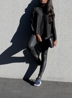 Minimal style   Black asymmetrical shirt + coated jeans + Nike Roshe Run sneakers + metallic holograph clutch in a casual chic outfit. By West African and Parisian blogger Iman.