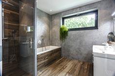 Stěny koupelny jsou ošetřeny hydro stěrkou, která dodává industriální charakter. Skvěle kontrastuje s obklady na vaně, podlaze a ve sprchovém koutě imitujícími dřevo.