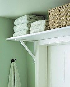 Install a shelf and brackets over the bathroom door to put that out-of-the-way spot to good use: Keep towels or bulky items there to save space in closets and cabinets.  Simple genius.