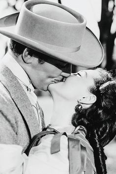 Clark Gable and Vivien Leigh, Gone With The Wind 1939. Love their slight smiles, sandwiched in the smooch. <3