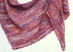 Taina is a triangular shawl worked from one corner to the long edge on the opposite side. It is worked in garter stitch and eyelet rows. It's made for the most beautiful skeins of sock yarn that you'd rather wear around your neck than on your feet. You can continue until you run out of yarn. A single skein of fingering weight sock yarn will produce a decent size shawl.