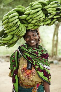 The Beautiful People of Africa! Lady carrying Green Bananas to Market.