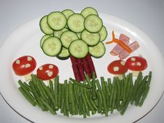 Kids healthy snack plate 2 cucumbers and small jerkey sticks (tree) Tomatoes cut in half and string cheese (Mushrooms), Baby carrot and a ham slice (Butterfly) and green bean grass