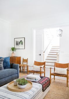 White room with leather armchairs and blue sofa