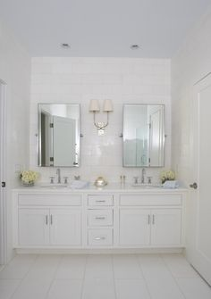white on white. single sconce in between two mirrors.