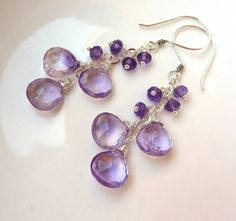 Lovely Lilac and Lavender Amethyst earrings! These earrings are a gorgeous cascade of small lavender to deep grape rondelles ending in a wonderful trio of Lilac Amethyst AAA briolettes. The verying shapes and shades make the earrings pop and give a fun feeling to these wonderful dangly ear ornaments! All wire wrapped by hand onto sterling silver chain and earwire. Enjoy!