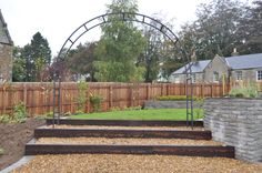 Metal arch adds to the contemporary feel of this stylish garden.