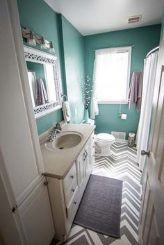 Wall color, maybe white or grey floor with chevron grey rugs, the sink can either be painted grey with turquoise touches or white with turquoise. Touches of grey decor around and grey or white towels