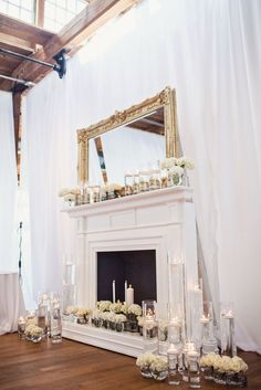 A beautiful ceremony backdrop at The Cotton Room - we love how the mantle is overflowing with candles + fresh flowers!