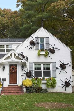 We're totally obsessed with this outdoor Halloween decorating look. To make spiders large enough to cover an entire house, ditch the foam balls and grab two half-sphere wire globes. They're large enough to make the spiders and weigh next to nothing—which makes these giant spiders super easy to hang. #giantdiyspiders #giantspidersonhouse #giantspiderdiy #halloweendecor #bhg