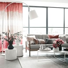 Grey living room with statement arc lamp and blush pink accents