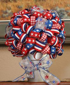 DIY 4th of July ribbon topiary by Corri Garza. Loops of ribbon attached to a foam ball with straight pins  #diy #4th_of_july #memorial_day #ribbon_topiary