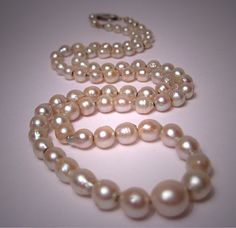 A Beautiful Antique Pearl Necklace, Art Deco Strand with White Gold Clasp. The necklace is composed of 80 genuine Salt Water Ocean Pearls graduating from about 7 1/2mm to about 4mm in diameter. They have a beautiful natural luster and the shape is semi-baroque. The clasp is Art Deco 14K white gold. Overall it measures about 17 inches long and lays beautifully on the neck.