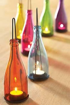 Simple DIY! LOVE this set of 6 colorful bottles to hang in your garden or on your patio.  Use tealights in the removable bottoms, and hang from branches or hooks.  Could use that glass cutting method with the string to create this with coke bottles!