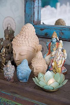 Beautiful simple altar space - Buddha heads-in our new house. I love the lotus candle holder