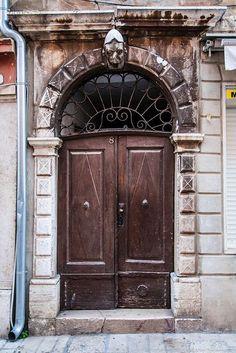 Old brown door. Left side is missing a flower. Beauty