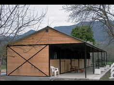"""5-Stall Shedrow Barn shown with: - 3:12 roof pitch - 13'2"""" overhang - 8' eaves - brown frame - T filler panels - grilled stall fronts - 4'x4' grilled windows & shutters - horseshoe blanket bars - Durango Ultra Cool metal roofing"""