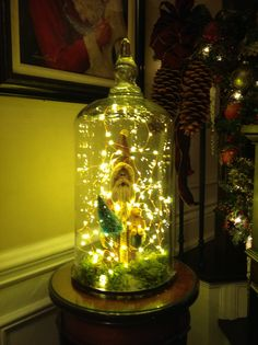 Clay Santa under a glass cloche with Restoration Hardware 'starry string lights'.