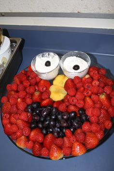 Elmo fruit tray: strawberries & rasberries for face, black grapes for mouth, sliced nectarine for nose, whip cream with grape for eyes inside small glass bowls