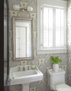Tone on Tone.  Love the wallpaper in this charming powder room!