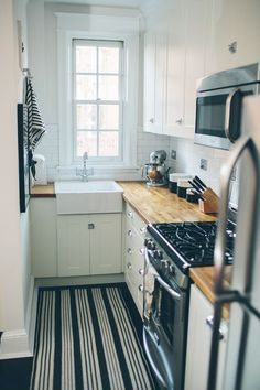 Cottage Kitchen with Wood counters, Surya Country Living Farmhouse Pinstripe Rug, Flat panel cabinets, Flush, L-shaped