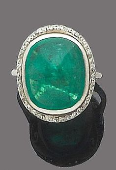 An emerald and diamond ring, circa 1920 The cabochon emerald, within a single-cut diamond surround, ring size L