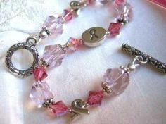 """This elegant bracelet in light pink and rose crystals sparkles from every angel. The center 11mm x 8mm STERLING SILVER oval bead is two sided with the word """"Survivor"""" engraved on one side and a ribbon engraved on the other side. A combinationof 6mm Swarovski rose ab bicone crystal beads, 8mm light pink faceted glass beads, and two sterling silver ribbon beads create the design of the bracelet.  $36.95 http://www.etsy.com/listing/176096724/breast-cancer-awareness-crystal-and?ref=related-0"""